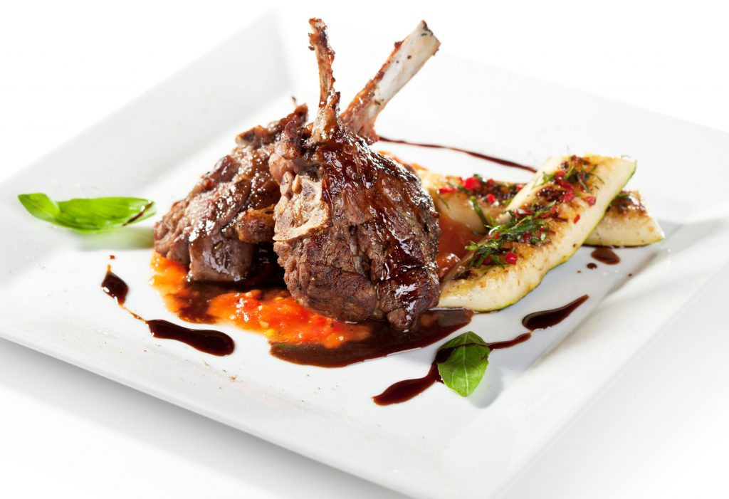 Thorpe Farms - Roasted lamb chops on tomato sauce garnished with vegetables and basil